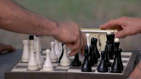Chessboard close up. Two old men playing chess with chess clock stock footage