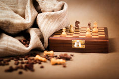 Chessboard and coffee beans. Selective focus on the knight Stock Photo