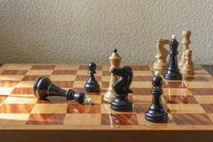 A chessboard with the defeated king on a textural background. Concept Stock Photography