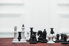 Chessboard with figures. On a wooden red table. Chess game concept Royalty Free Stock Photos