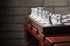 Chessboard with figures. On a wooden red table. Chess game concept Royalty Free Stock Photo
