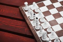 Chessboard with figures. On a wooden red table. Chess game concept Stock Photos