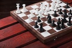 Chessboard with figures. On a wooden red table. Chess game concept Royalty Free Stock Photography