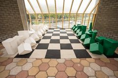 Chessboard on the floor. In a building there is a large chessboard on the floor with artificial objects stock photos