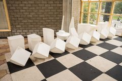 Chessboard on the floor. In a building there is a large chessboard on the floor with artificial objects stock photo
