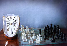 Chessboard game and Dali-like clock. A melting and distorted Dali clock and a chessboard with a game in progress royalty free stock images