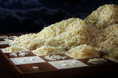 Chessboard with growing heaps of rice grains, concept of exponen Royalty Free Stock Images