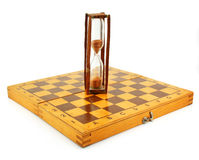 Chessboard and hourglass. Isolated on a white background Royalty Free Stock Images