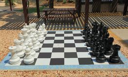 Chessboard with huge black and white chess figures for outdoor playing. Nice backgrounds. Aruba royalty free stock photo