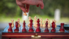 Chessboard and human hand. Player arrange chess figures Stock Image