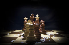 Chessboard and pieces under light Royalty Free Stock Photos