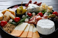 Chesse盛肉盘用乳酪,熏火腿,蕃茄,坚果 健康吃,牛奶店、chesses和肉 开胃小菜开胃菜 软制乳酪, moz 免版税图库摄影
