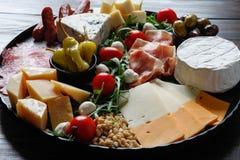 Chesse盛肉盘用乳酪,熏火腿,蕃茄,坚果 健康吃,牛奶店、chesses和肉 开胃小菜开胃菜 软制乳酪, moz 免版税库存照片