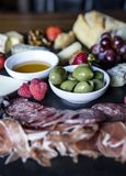 Chesse Board with Olives and Charcuterie. Vertical photograph of a cheese board with Charcuterie and fruit stock photos