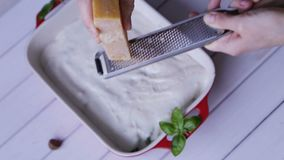 Chesse grattato del parmigiano sulla pasta dei cannelloni con basilico archivi video