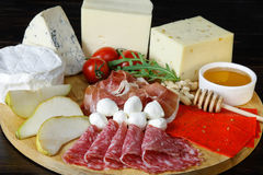 Chesse platte with different cheeses, meats on wooden board Stock Photos