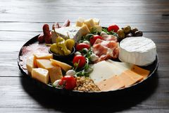 Chesse platter with cheese, prosciutto, tomato, nuts. Healthy eating, dairy, chesses and meat. Antipasti appetizer. Camembert, moz stock photos
