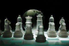 Chessfigures de cristal e um globo de vidro Fotografia de Stock Royalty Free