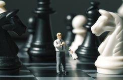 Chessman and chess figures on game board. Playing chess with miniature doll macro photo. Man explains chess game rules. Teacher puppet on chessboard. Checkmate royalty free stock photo