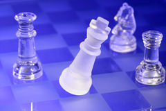 Chessmen di vetro all'indicatore luminoso blu Fotografia Stock