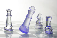 Chessmen di vetro all'indicatore luminoso blu Fotografie Stock