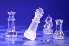Chessmen di vetro all'indicatore luminoso blu Immagine Stock