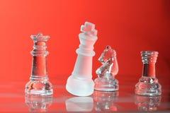 Chessmen di vetro alla luce rossa Fotografie Stock Libere da Diritti