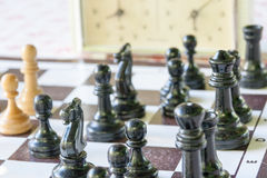 Chessmen and hours on a board Stock Photography