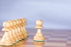 Chesspawns on the left are guided by the major pawn on the right. Outstanding chesspawn on the right is focused Stock Photo