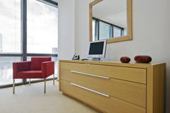 Chest of drawers in birch. With red armchair and mirror stock photo