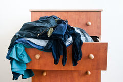 Chest of drawers with dangling clothes Stock Photo