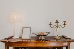 Chest of drawers with a lamp candelabra and a vase against a white wall- Image stock images