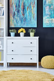 Chest of drawers in living room. White chest of drawers in modern living room decorated with paintings Stock Images