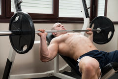 Chest Exercise On Bench Press In Gym. Muscular Man Doing Heavy Weight Exercise For Chest On Bench Press In Gym Stock Photography