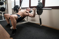 Chest Exercise On Bench Press In Gym. Muscular Man Doing Heavy Weight Exercise For Chest On Bench Press In Gym Royalty Free Stock Photo