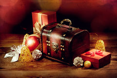Chest, gifts and other christmas decoration on old wooden table Stock Image