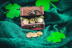A chest with gold coins on a green background. Clover leaves. St.Patrick 's Day. A chest with gold coins on a green background. Clover leaves. St.Patrick 's Day Stock Photos