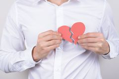 Chest pain ache attack heartache health unhealthy care healthcare problem concept. Cropped close up photo of small heart in hands. Isolate grey background stock photography