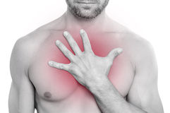 Chest pain. Closeup of shirtless bearded muscular Caucasian man with chest pai pressing hand on chest on white background royalty free stock images