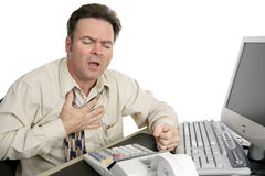 Chest Pain at Work. A man in his forties experiencing chest pain while working in his office.  Isolated on white Royalty Free Stock Image