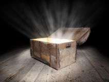 Chest of treasure. Ancient wooden treasure chest with the strong glow from inside royalty free stock photography