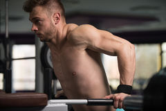 Chest And Triceps Exercise on Parallel Bars. Young Muscular Fitness Bodybuilder Doing Heavy Weight Exercise For Triceps And Chest on Parallel Bars In The Gym Stock Photo