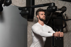 Chest Workout Cable Crossover. Handsome Man Is Working On His Chest With Cable Crossover In A Modern Gym Royalty Free Stock Photos