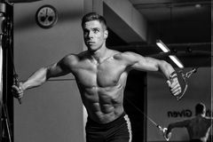 Chest Workout Cable Crossover. Young Bodybuilder Is Working On His Chest With Cable Crossover In A Dark Gym royalty free stock photos