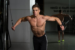 Chest Workout Cable Crossover. Young Bodybuilder Is Working On His Chest With Cable Crossover In A Dark Gym royalty free stock images