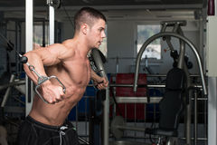Chest Workout Cable Crossover. Young Bodybuilder Is Working On His Chest With Cable Crossover In A Dark Gym stock photography