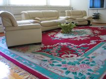 Chesterfields on carpet. Light chesterfield, glass table on many-coloured carpet Stock Image