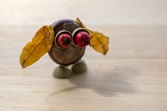 Chestnut animal on wooden stump, owl made of chestnut, acorn, yellow leaves and red hawthorn fruits, funny bird. Chestnut animal on wooden stump, owl made of royalty free stock photo