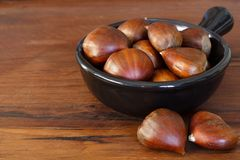 Chestnut in black bowl on wooden table Royalty Free Stock Photography