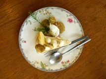 Chestnut with caramel salted cake serving with cookies on flower pattern plate. On timber table stock image